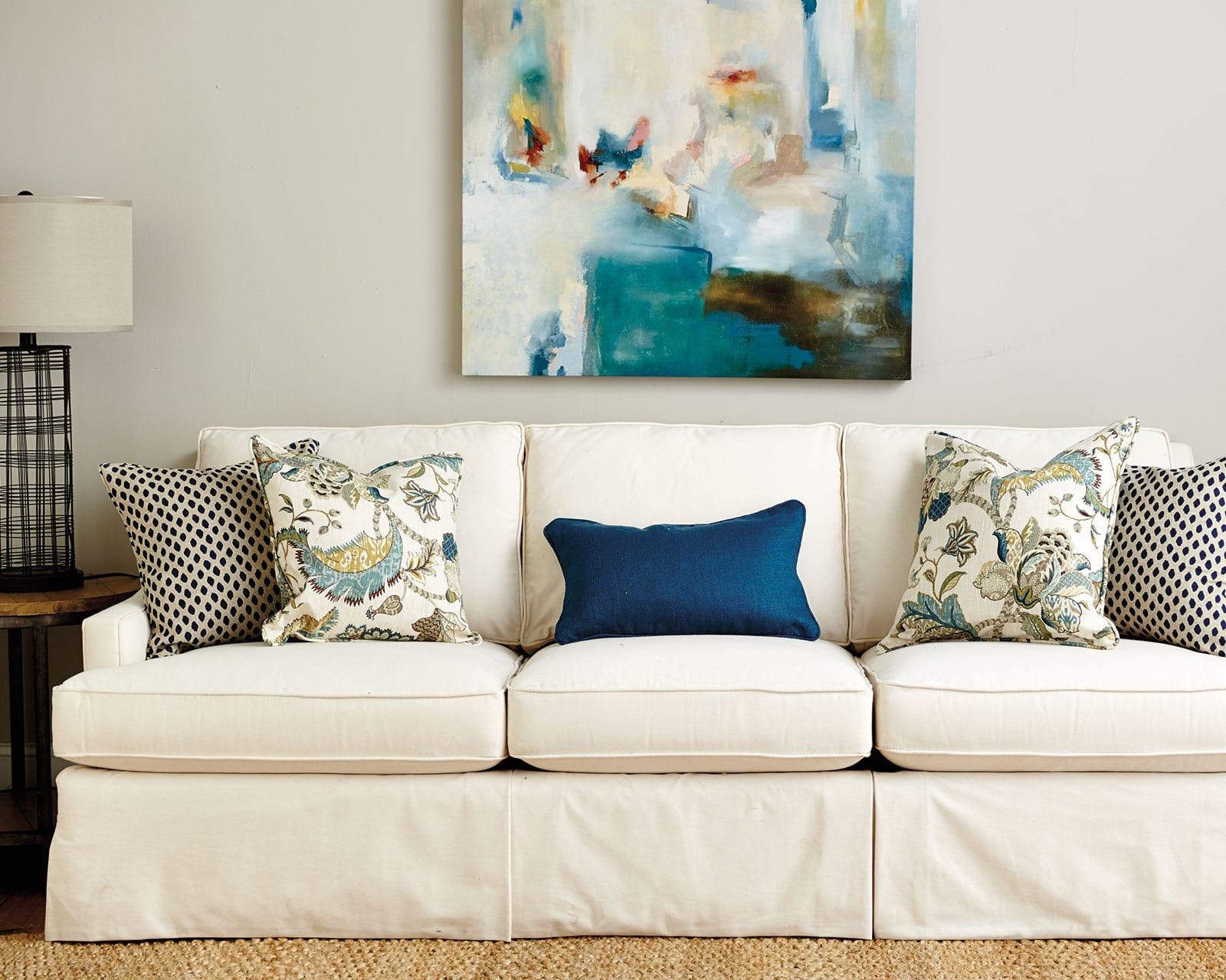 Фон картины дублируется в обивке кресла и диванных подушках, фон стены нейтральный